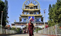 A Tibetan Buddhist monk walks in front of the Golden Temple inside the Nyingmapa Monastery in Bylakuppe, southwest of Bengaluru, previously known as Bangalore, December 4, 2014. Credit: REUTERS/Abhishek N. Chinnappa