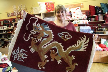 Colourful carpets: New Plymouth Trade Aid shop manager Donna Stonnell holds up one of the Tibetan carpets.