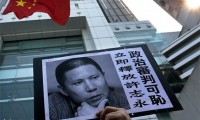 A placard with a photo of legal scholar Xu Zhiyong is raised by a demonstrator, protesting against a Chinese court's decision to sentence him in prison, outside the Chinese liaison office in Hong Kong. (AP/Vincent Yu)