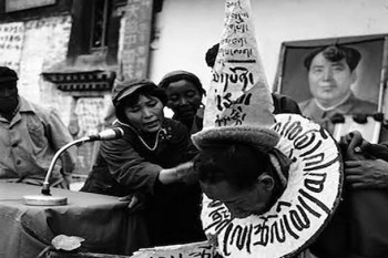"Tsadi Tseten Dorjee is subjected to a fierce ""struggle session"" by Lugug Achak, the lady wearing a military cap, inside the Jokhang Temple courtyard. Lugug Achak, prior to 1959, was a beggar, commonly known by the name, Lugug Tangpo (beggar). The long placard on Tsadi Tseten Dorjee's chest reads: ""Murderer of the proletariat, key conspirator of the uprising and counter-revolutionary fugitive."" Photo: Tibet Museum"