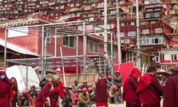 Government-hired workers tasked to demolish Larung Gar's cabins seen at rest. Larung Gar's monks and nuns amble by, resigned against the larger forces affecting them. Image Credit: David Chan