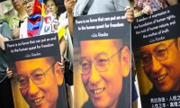Participants, one wearing a Tibetan flag, hold photos of Liu Xiaobo during a vigil honoring Xiaobo's legacy and to protest continued human rights abuses in China. (Photo: AP)